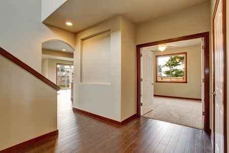 Empty hallway with hardwood floor, white walls. View of other room from the corridor Stock Photo