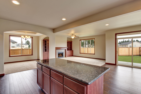 kitchen island: Open floor plan interior with carpet floor and fireplace. View from kitchen and island at the foreground