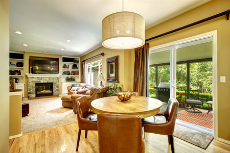 round chairs: Living room interior with round dining table and leather chairs, view of walkout deck