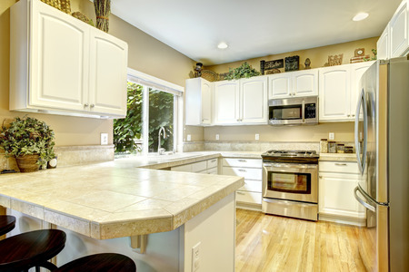 cabinets: White kitchen cabinets with steel appliances and light tone hardwood floor