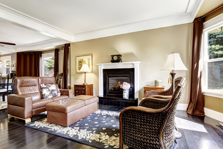 fireplace home: Luxury home interior in brown tones with fireplace, antique chairs, leather couch and ottoman Stock Photo