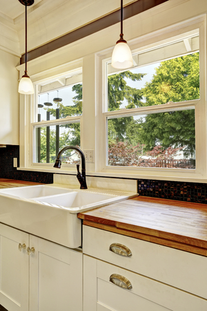 trims: Kitchen interior in white tones with hardwood counter top and black tile back splash trim.