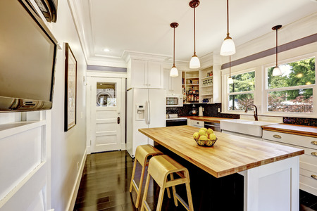 Kitchen interior in white tones with hardwood counter top, kitchen island, pendant lights and black tile back splash trim.