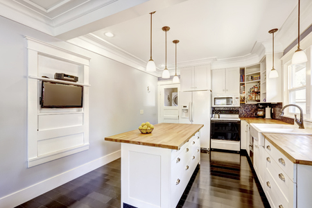 splash back: Kitchen interior in white tones with hardwood counter tops, kitchen island and black tile back splash trim. White coffered ceiling with pendant lights make room more elegant.