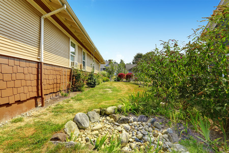 back yard pond: Backyard garden of American craftsman house. Also there is a Small decorative pond with rocks in the garden Stock Photo