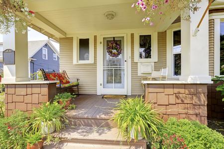 Amerikaanse ambachtsman huis exter. Gezellige overdekte veranda met witte zuilen en veel bloemen aan de voorkant.