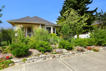 curb appeal: View of American craftsman house with lots of greenery and flower bed in the front.