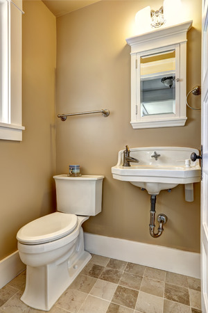 Antique style bathroom interior with tile floor, white wash basin and toilet.