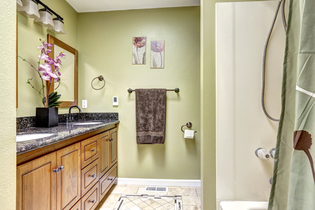 tile flooring: Cozy bathroom interior in ivory tones with dark granite counter top, tile flooring and  orchid pot on the cabinet