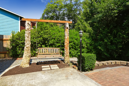 back yard: Wooden swing bench outside in the green back yard. Stock Photo