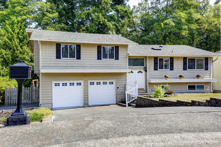 white trim: Beige siding  house exterior with  white trim. View of two garage spaces with asphalt driveway Stock Photo