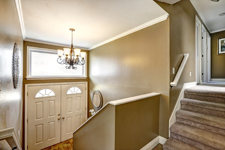 white trim: Entryway in small American home with mocha walls and white trim, staircase with carpet , white entrance door and beautiful chandelier on the ceiling Stock Photo
