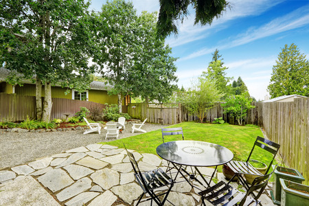 lawn area: Fenced back yard with stone floor patio area and white adirondack chairs. Also green lawn, trees and flower bed in the yard. Northwest, USA. Stock Photo