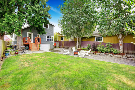 fire pit: Small American house exterior. Fenced back yard with patio area and white adirondack chairs with fire pit. Also green lawn, trees and flower bed in the yard. Northwest, USA. Stock Photo