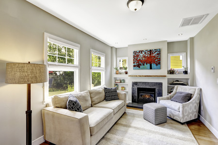 Small yet nice and cozy white living room with fireplace and comforatble beige sofa. Northwest, USA