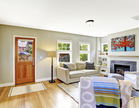 entryway: Small yet nice and cozy white living room with fireplace and comforatble beige sofa. The room is connected with entryway, view of brown wooden entrance door. Northwest, USA.