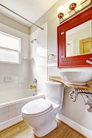 vessel sink: Refreshing bathroom interior. Red cabinet with mirror and white vessel sink. Northwest, USA.