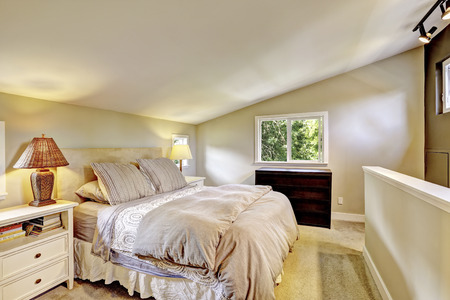 Nice upstairs bedroom  interior with king size bed and vaulted ceiling. Stock Photo