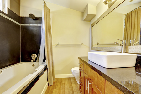 vessel sink: Bathroom with contrast wall. Black wall trim and white bath tub. Cabinet with granite top and vessel sink. Northwest, USA Stock Photo