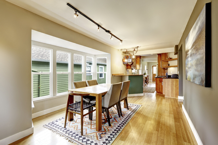 Cozy creamy tones dining room with wooden table set. There is old ethnic pattern rug on hardwood floor and contrast wall with mocha paint. Northwest, USA 版權商用圖片