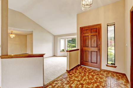 View of entryway with brown tile floor and vaulted ceiling. The room is connected with unfurnished empty room. Northwest, USA