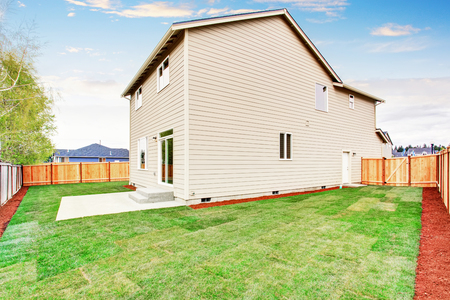 american house: American house fenced back yard exterior  with well kept lawn Stock Photo