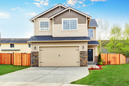 curb appeal: American house exterior with beige trim, garage with concrete driveway and brown fence with well kept lawn around
