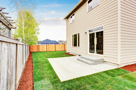 fenced: American house fenced back yard exterior  with well kept lawn Stock Photo