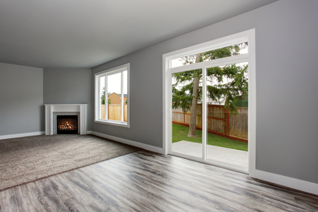 glass doors: Grey living room interior with fireplace. Windows and Glass doors overlooking the back yard.