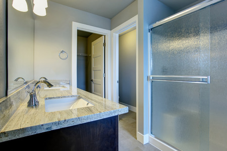 Bright bathroom interior with glass shower and tile floor and walk in closet.