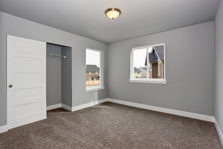 Small basement room interior with grey walls and white trim. The room with walk in closet. Stock Photo