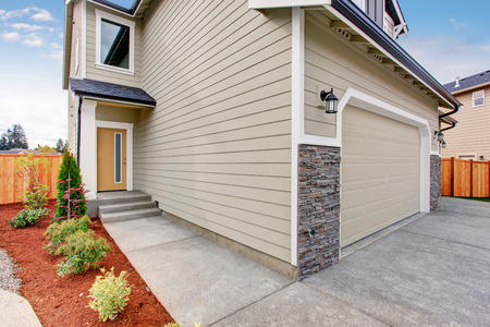 walkway: Beige house with white trim. Concrete walkway to the entrance door.