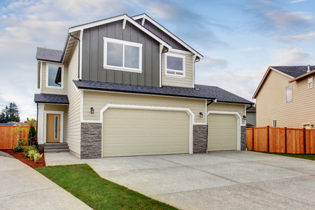 curb appeal: American house exterior with two garage spaces and concrete floor driveway.