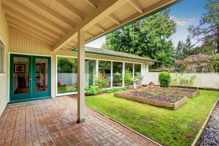 Small vegetable garden with risen beds in front of the house. Tile walkway leads to the entrance door. Stock Photo