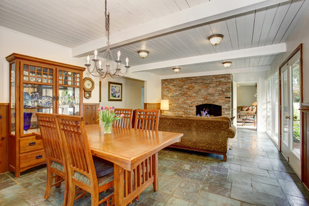 House interior with open floor plan. Dining room with wooden furniture set, living room with brick wall and fireplace.