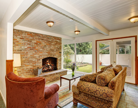 french doors: View of the living room area with white wooden ceiling and brick wall with fireplace. French doors leading to the vegetable garden.