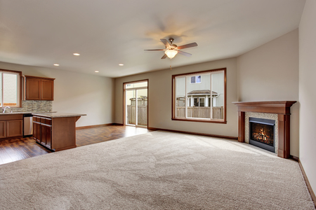 unfurnished: Large empty living room interior with carpet floor and fireplace. View of kitchen room.
