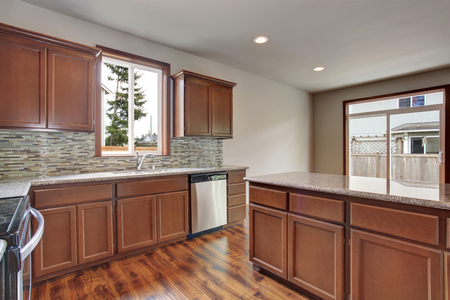 cabinets: Modern kitchen room interior in empty house. Also dark brown cabinets, granite counter tops and hardwood floor. Stock Photo