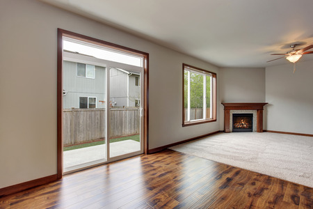 unfurnished: Large empty living room interior with carpet floor, fireplace and glass sliding doors leading to back yard.