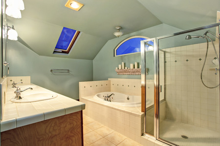 skylights: Old ivory bathroom with vaulted ceiling and skylights. View of glass shower with tile wall trim and white bath tub  decorated with candles on the shelf above. Northwest, USA Stock Photo