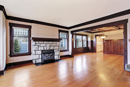 unfurnished: Empty Family room with white ceiling and dark brown trim, antique stone fireplace and hardwood floor. View of unfurnished room with wood paneled walls. Northwest, USA