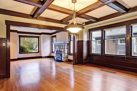 stone fireplace: Empty room with wood paneled walls and coffered ceiling.  View of family room with old fireplace with stone trim.  Northwest, USA Stock Photo