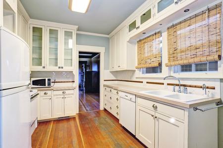 northwest: White empty simple old kitchen room with pastel blue ceiling  and hardwood flooring. Northwest, USA Stock Photo