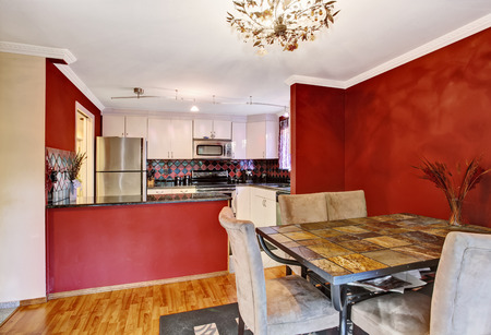 Dining area connected to kitchen with red walls, hardwood floor and vintage chandelier. Northwest, USA