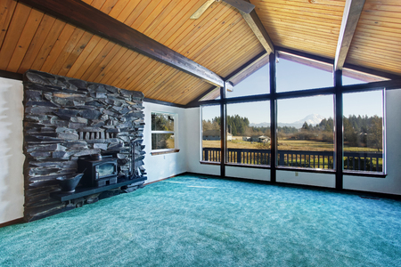 pitched: Empty living room with turquoise carpet floor in luxury house with large windows and pitched wooden ceiling. View of antique fireplace with stone wall. Northwest, USA