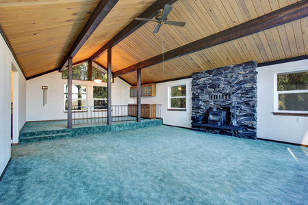 stone fireplace: Empty living room with turquoise carpet floor in luxury house with large windows and pitched wooden ceiling. View of antique fireplace with stone wall. Northwest, USA