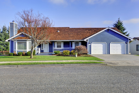 white trim: Curb appeal one level American house with blue and white trim and wooden porch. Also two garage doors and driveway. Northwest, USA Stock Photo