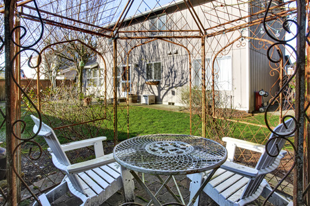 View of old metal gazebo with table and two adirondack chairs in the back yard. Northwest, USA
