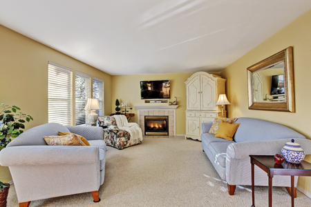 antique: Elegant family room interior with light blue sofas, antique cabinet and fireplace. Northwest, USA Stock Photo