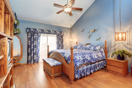 vaulted ceiling: Adorable wooden bedroom interior in marine style. The room has vaulted ceiling, hardwood floor and amazing blue floral bedding and curtains.